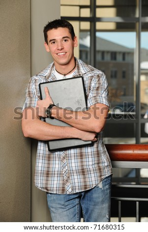 Young man holding his laptop computer with college buildings as background - stock photo