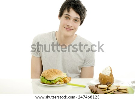 Young man holding in front lots of cookies and a big hamburger. Choosing between chocolate, cupcakes, biscuits and a burger. Trying to get fat eating fast food and lots of sugar - stock photo
