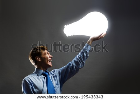 Young man holding light bulb in hand - stock photo
