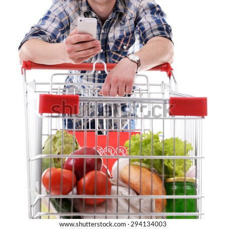 Young man holding mobile phone and shopping cart isolated on white - stock photo