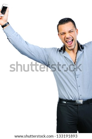 Young man holding mobile phone and winning something - stock photo