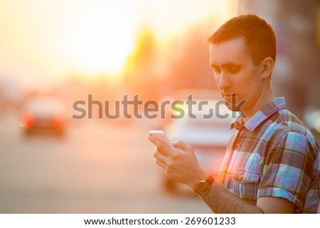 Young man holding mobile phone, using smartphone app, scrolling, looking at screen, standing on sunny street with transport vehicles on the background - stock photo
