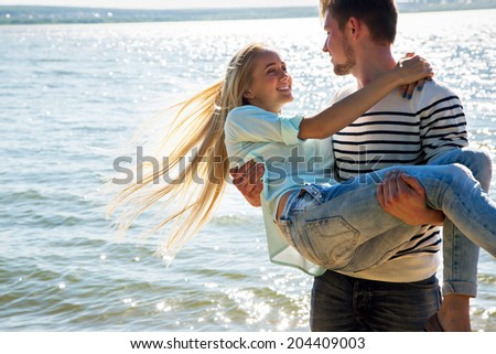 Young man holding on the hands his a cute girlfriend - stock photo