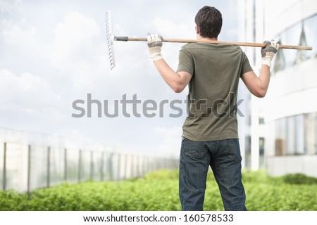 Young man holding rake on his shoulders and looking at green plants in roof top garden in the city - stock photo
