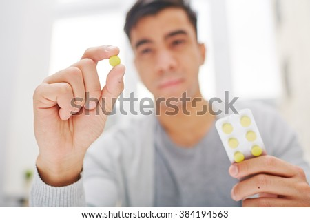 Young man holding round yellow pill - stock photo