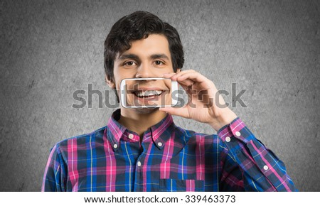 Young man holding smartphone with smile on screen - stock photo