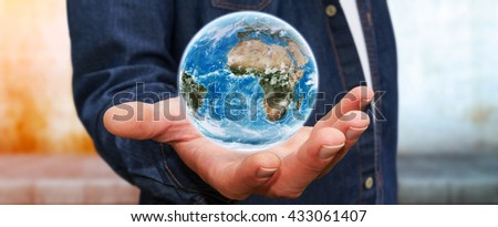 Young man holding the blue planet earth in his hand 'elements of this image furnished by NASA' '3D rendering' - stock photo