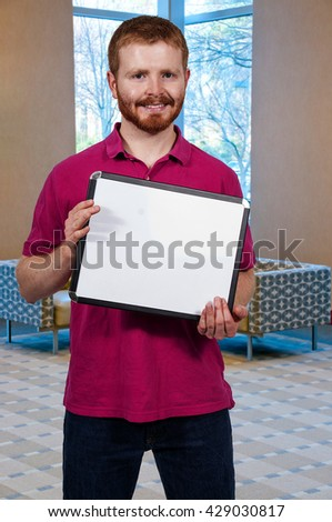 Young man holding up a blank sign - stock photo