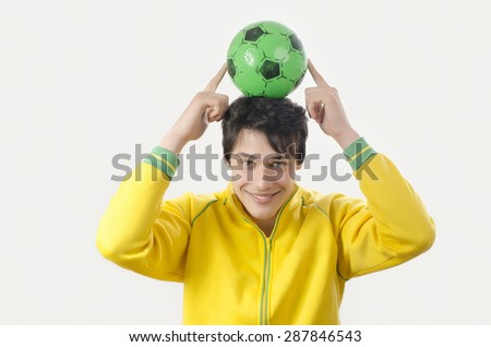 Young man holding up a football ball. Attractive man holding a ball in the hands over his head. Isolated on white. - stock photo