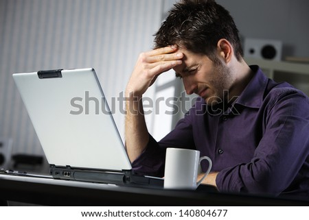 Young man holds her aching head while seated at a laptop - stock photo