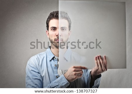 young man holds transparent panel in front of his face - stock photo