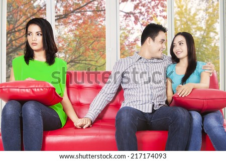 Young man hugging his girlfriend and holding hands his best friend with autumn background - stock photo