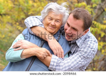 Young man hugging senior woman - stock photo