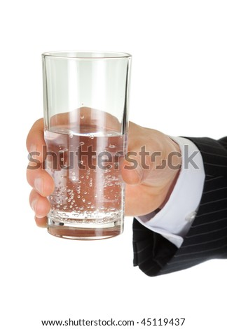 young man in a black business suit holds a glass of water on a white background - stock photo
