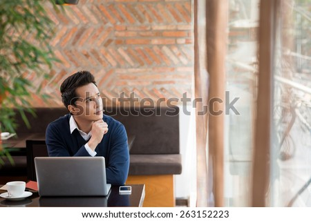 Young man in a cafe thinking over idea for the new blog post - stock photo