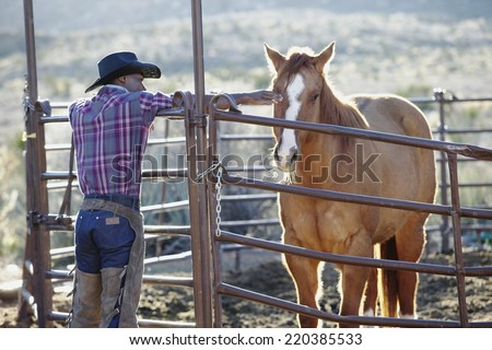 Young man in a cowboy outfit petting a horse - stock photo