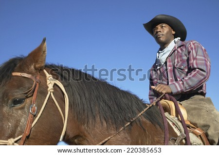 Young man in a cowboy outfit riding a horse - stock photo
