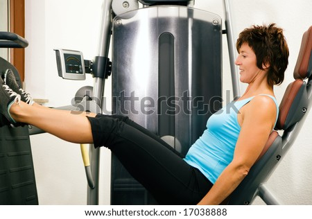 Young man in a gym training his back muscles on a machine Mature woman exercising her legs at a machine in the gym - stock photo