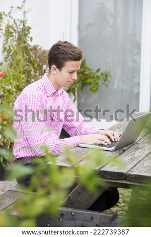 young man in a red shirt sitting outside with a laptop - stock photo