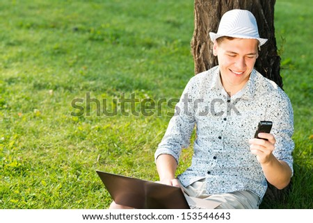young man in a summer park on the grass with cell phone - stock photo