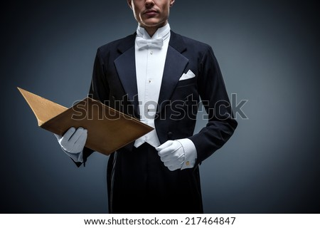 Young man in a tuxedo with folder - stock photo