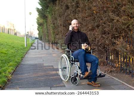 young man in a wheelchair talking on the phone with a coffee - stock photo