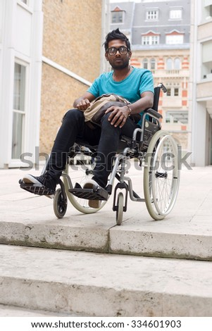 young man in a wheelchair waiting at the top of steps - stock photo