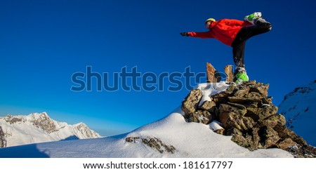 Young man in a yoga pose in winter mountains - stock photo