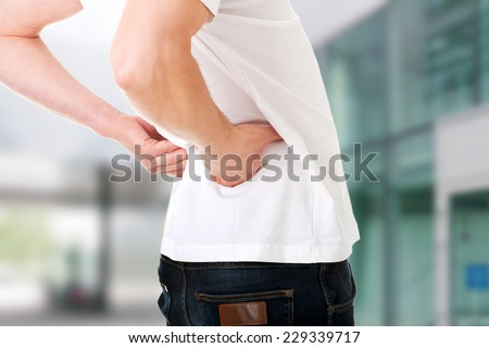 Young man in agony with back pain - stock photo