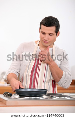 Young man in apron cooking - stock photo