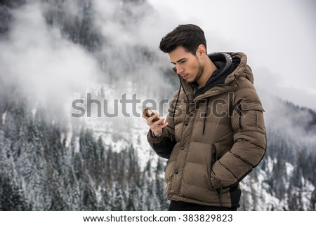 Young man in at mountain using cell phone - stock photo