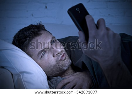 young man in bed couch at home late at night with intense face expression using mobile phone in low light watching online porn enjoying alone in internet addiction - stock photo