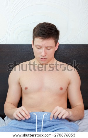 Young man in bed having problems with potency looking at his penis under pants , Worried rejected man having trouble with erection failure - stock photo