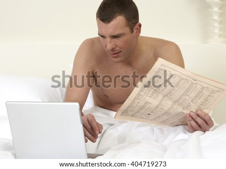 Young man in bed, working on laptop - stock photo