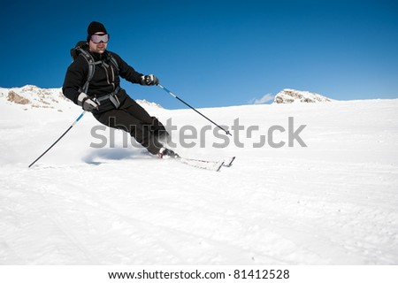 young man in black clothing skiing on mountain slope - stock photo