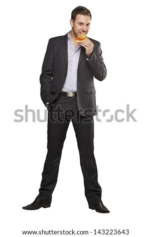 Young man in black suit eating pizza against white background - stock photo