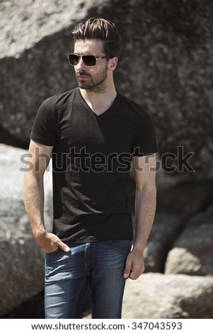Young man in black t-shirt posing on rocks - stock photo