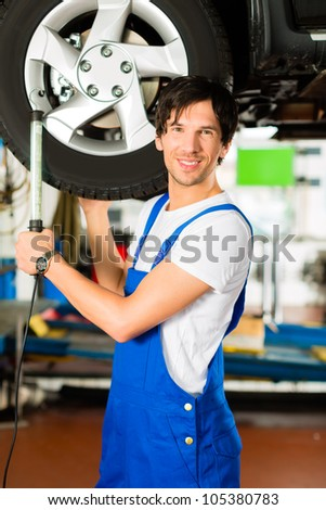 Young man in blue overall - mechanic - working with lamp on jacked car in a service station - stock photo