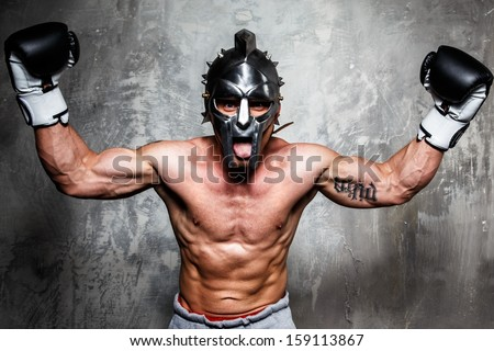 Young man in boxing gloves and gladiator helmet posing  - stock photo