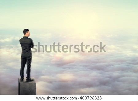 Young man in business suit, standing on concrete column above clouds. - stock photo