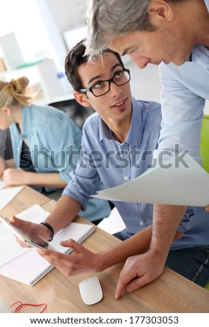 Young man in business training school with teacher - stock photo