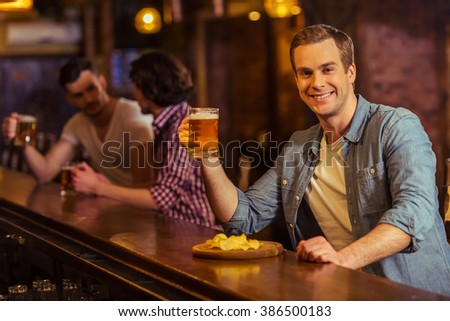 Young man in casual clothes is smiling, looking at camera and drinking beer while sitting at bar counter in pub, in the background two other men - stock photo