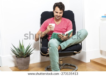 Young Man in Casual Clothing Sitting on Black Chair While Reading a Book and Holding a Glass of Drink. - stock photo