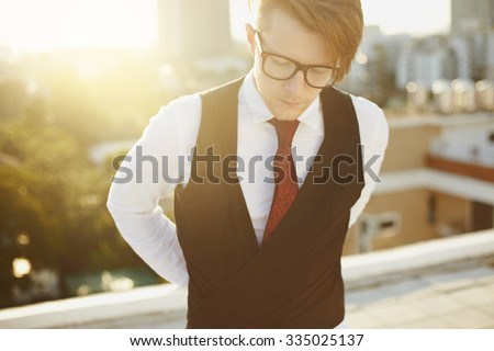 Young man in casual fashion hipster stylein glasses, and cityline on background - stock photo