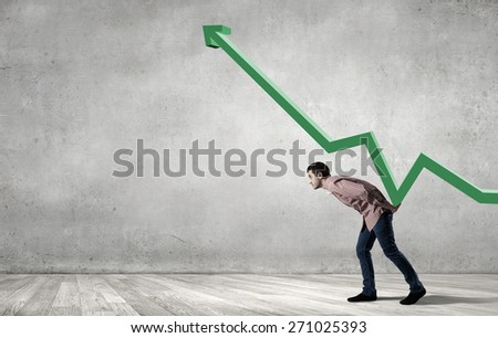 Young man in casual supporting increasing graph - stock photo