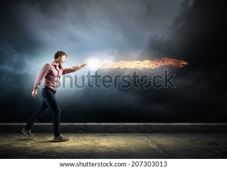 Young man in casual throwing fire ball - stock photo
