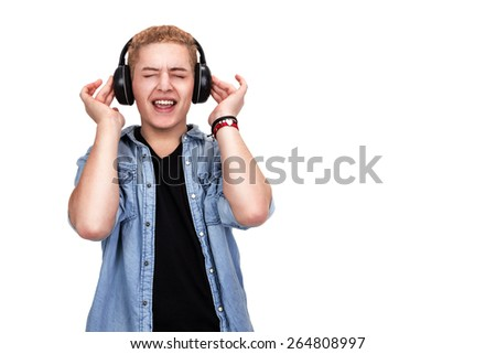 Young man in casual, trendy clothing listening to music and touching wireless headphones with eyes closed and an ecstatic expression, isolated on white - stock photo