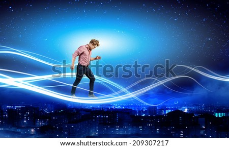 Young man in casual walking on cloud high in sky - stock photo