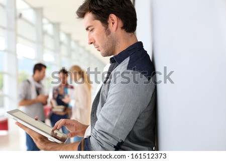 Young man in college campus connected on tablet - stock photo