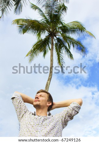 Young man in colorful shirt resting under a palm tree - stock photo